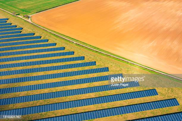 drone view of a field of solar panels - business finance and industry stock pictures, royalty-free photos & images