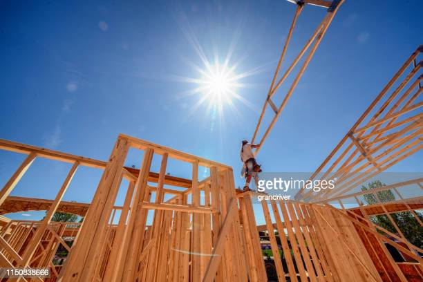 drone view of a home being framed by carpenters - home ownership stock pictures, royalty-free photos & images