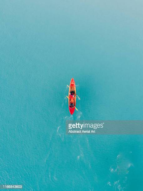 drone view of a red kayak in turquoise ocean water, barbados - single object stock pictures, royalty-free photos & images