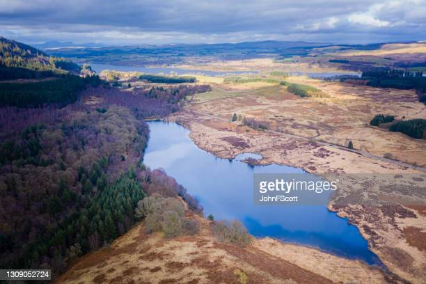 drone view of a scottish loch on an overcast day - johnfscott stock pictures, royalty-free photos & images