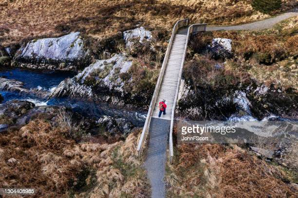 drone view of a senior man using on a footbridge - johnfscott stock pictures, royalty-free photos & images