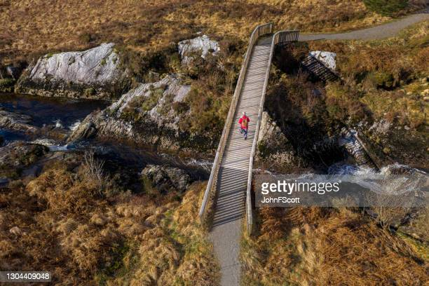 drone view of a senior man walking on a footbridge - johnfscott stock pictures, royalty-free photos & images