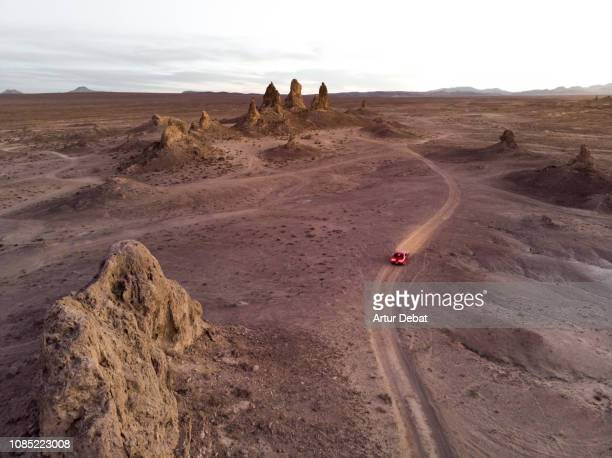 drone view of american car driving through the rock formations in the california desert. - route 66 stock photos and pictures