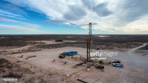 drone view of an oil or gas drill fracking rig pad with beautiful cloud filled sky - west direction stock pictures, royalty-free photos & images