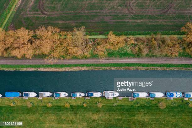drone view of boots moored on river - riverbank stock pictures, royalty-free photos & images