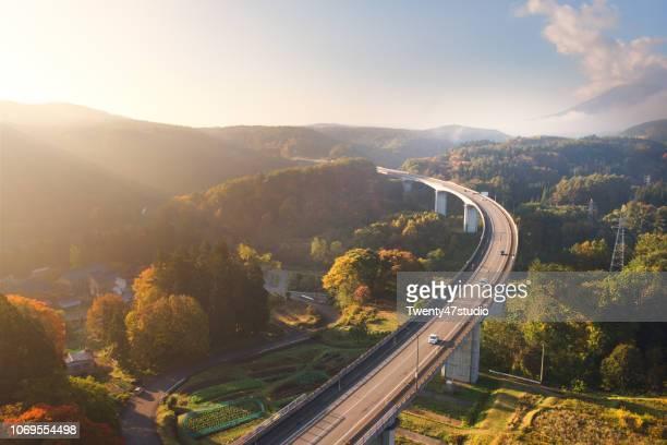 drone view of bridge through autumn forest in morning - 新潟県 ストックフォトと画像