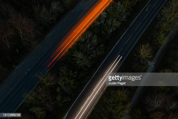 drone view of cars moving in different directions at night - illuminated stock pictures, royalty-free photos & images