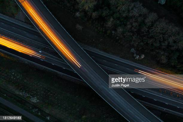 drone view of cars moving in different directions at night - direction stock pictures, royalty-free photos & images