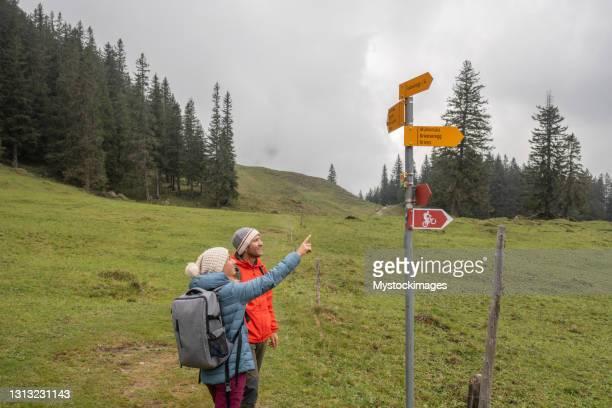 登山道でハイキングカップルのドローンビュー、方向標識を見るために停止 - トレイル表示 ストックフォトと画像