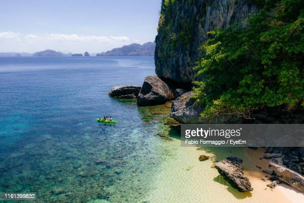 drone view of couple kayaking in sea on sunny day - philippines stock pictures, royalty-free photos & images