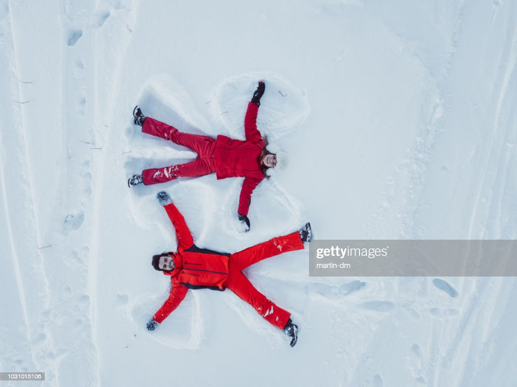 Drone view of couple making snow angel : Stock Photo