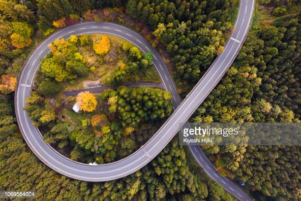 drone view of curve road through autumn forest on mountain - drone point of view stock pictures, royalty-free photos & images