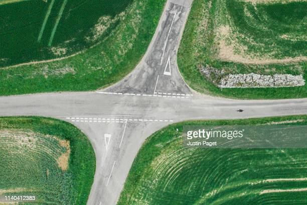 drone view of cyclist coming up to crossroads - crossroad stock pictures, royalty-free photos & images
