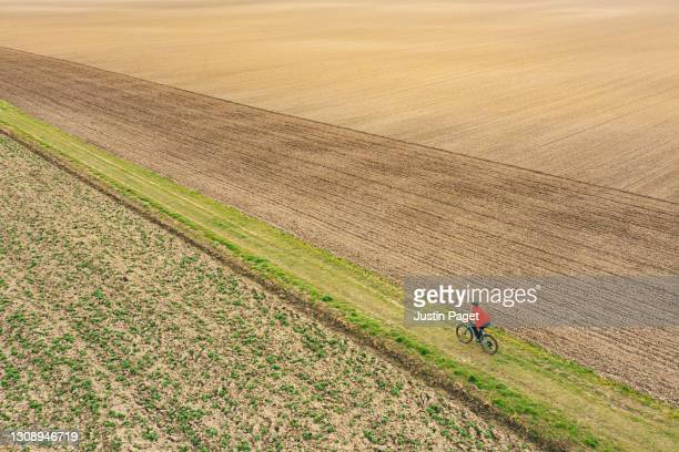 drone view of cyclist on rural track - red stock pictures, royalty-free photos & images