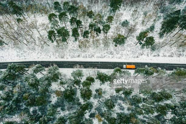 drone view of orange lorry on road through snowy forest - remote location stock pictures, royalty-free photos & images