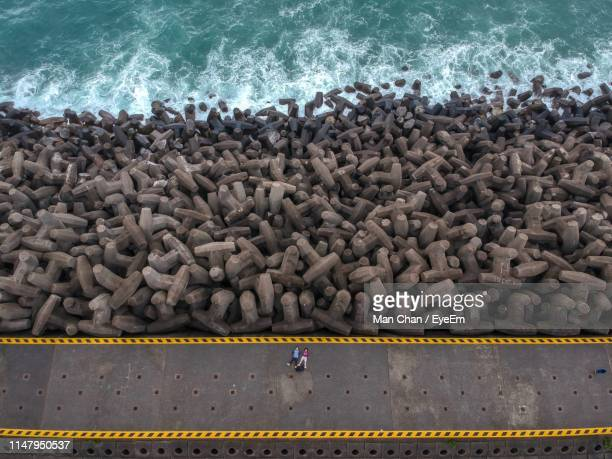 drone view of people lying on promenade by groyne - 防波堤 ストックフォトと画像