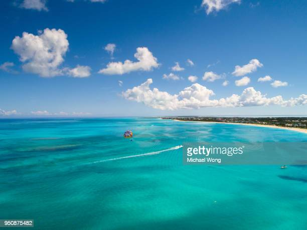 drone view of perfect day parasailing in perfect clear blue water - turks and caicos islands stock pictures, royalty-free photos & images