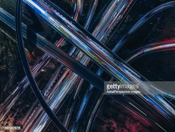drone view of road intersection, overpass and city traffic at night - on the move stock-fotos und bilder