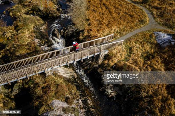drone view of senior man on rural footbridge - johnfscott stock pictures, royalty-free photos & images
