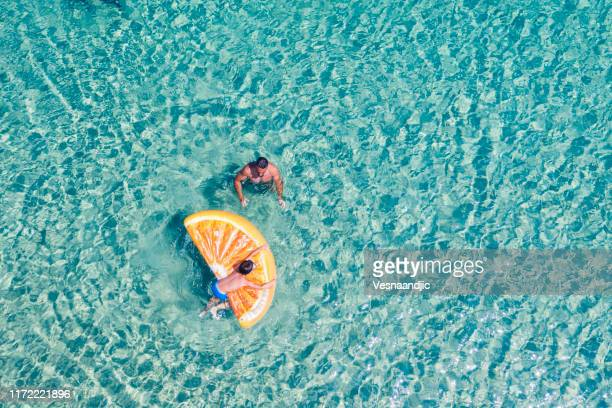 drone view of swimming people - lagoon stock pictures, royalty-free photos & images
