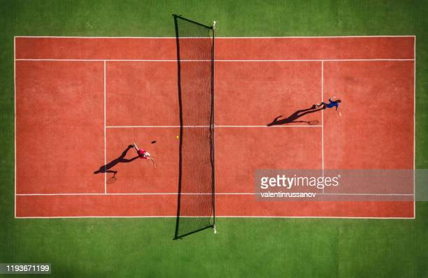 drone view of tennis match from above with player's shadow - taking a shot sport stock pictures, royalty-free photos & images