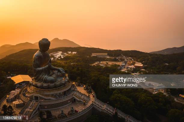 drone view of the big buddha is lit in the evening - east asia stock pictures, royalty-free photos & images