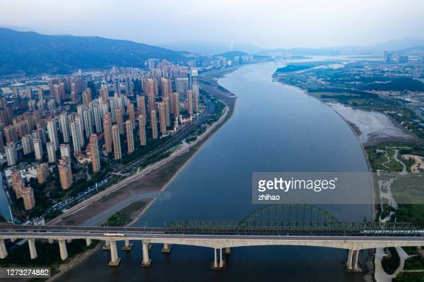 a drone view of the railway bridge connecting the two banks of the river - fuzhou stock pictures, royalty-free photos & images