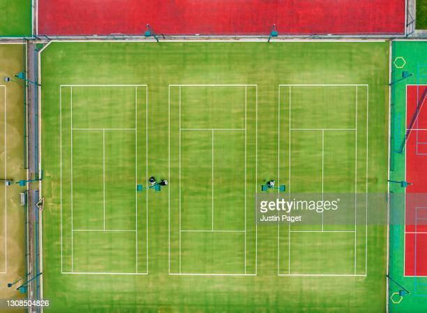 drone view of three green tennis courts - tennis tournament stock pictures, royalty-free photos & images