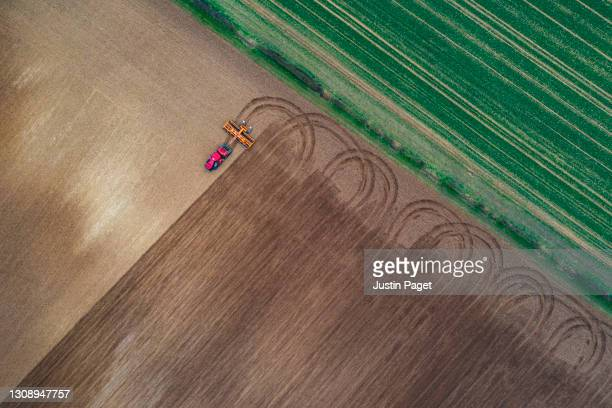 drone view of tractor ploughing a field - crop stock pictures, royalty-free photos & images