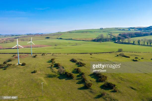 drone view of two wind turbines on farmland - johnfscott stock pictures, royalty-free photos & images