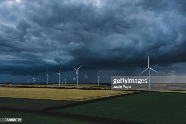 drone view of wind farm under stormy skies - scenics stock pictures, royalty-free photos & images
