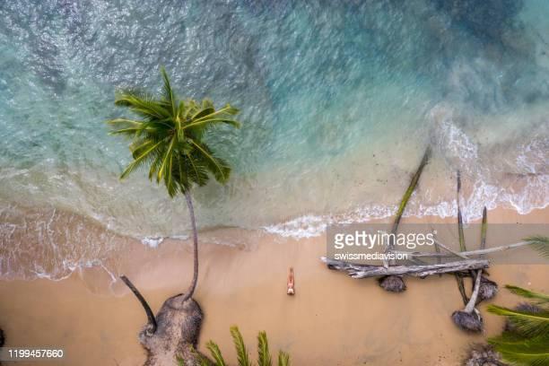 vista de drone de mujer relajándose en la playa de arena dorada - costa rica fotografías e imágenes de stock