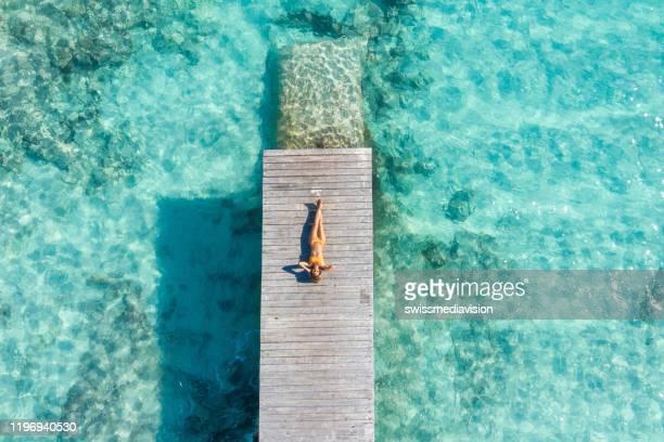 vue de drone de femme détendant sur la jetée en bois au-dessus de la mer tropicale - parasol de plage photos et images de collection