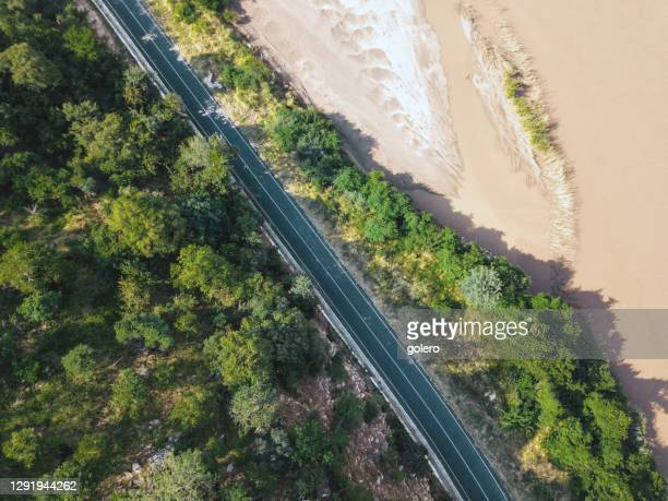 drone view on litttle road at zambezi river side - zambezi river stock pictures, royalty-free photos & images