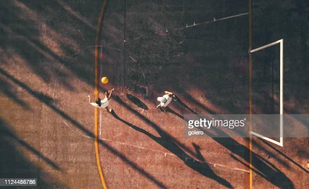 vista de drone no homem jogando futebol com teengage menina - equipamento esportivo - fotografias e filmes do acervo