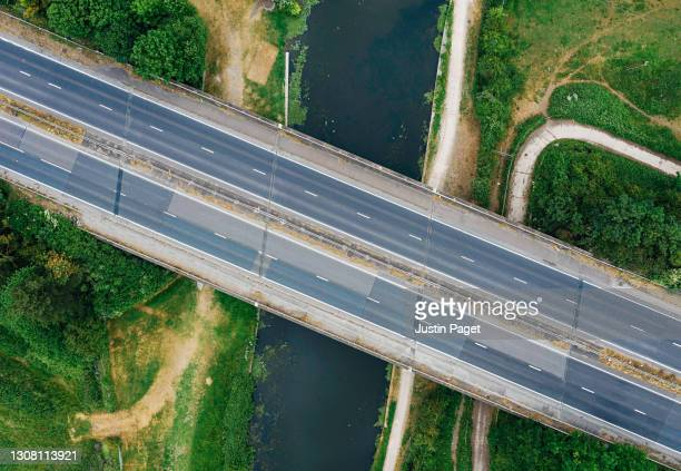 drone view over empty major road over river - drone point of view stock pictures, royalty-free photos & images