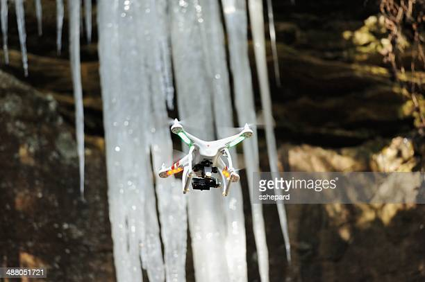 Drone with camera flying near icicles
