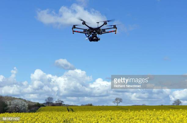 drone with camera in field - drone photos et images de collection