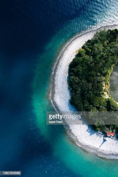 Drone's eye view of ring-shaped island with turquoise water, Japan