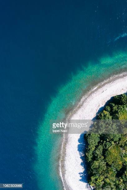 drone's eye view of ring-shaped island with turquoise water - insel stock-fotos und bilder