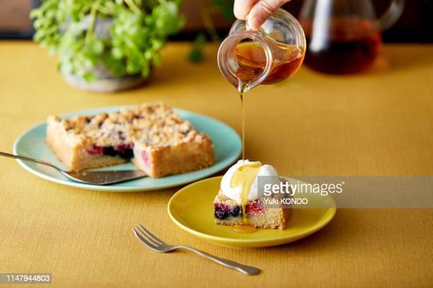 druppel esdoorn op crumble cake met verse room. - vierkant tweedimensionale vorm stockfoto's en -beelden