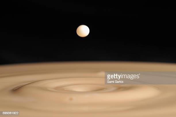 Drop of milk splashing into coffee mixed with milk