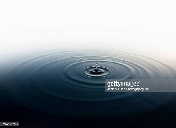 Drop of water rippling in still pool