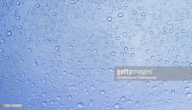 droplets of rain on a blue cloth - nylon stock pictures, royalty-free photos & images