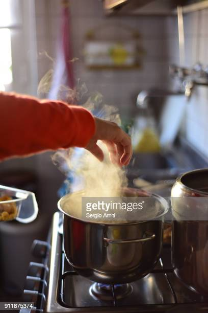 Dropping raw tortellini into a pot with boiling soup