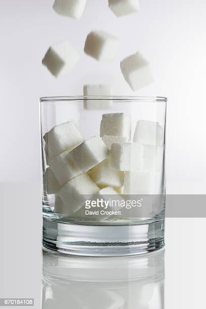 Dropping sugar cubes into cocktail glass