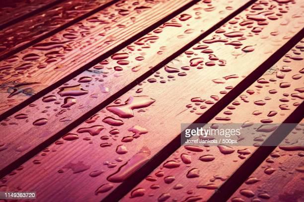 drops of water on a wooden table - schrägansicht stock-fotos und bilder