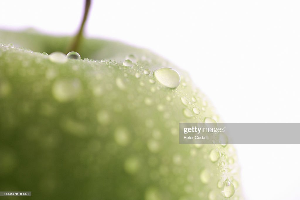 Drops of water on green apple, close-up : Stock Photo