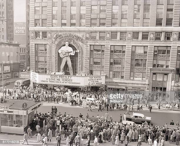 Droves of fans and curious Sunday afternoon strollers crowd outside the Paramount Theater where a 40foot figure of rock 'n' roll idol Elvis Presley...