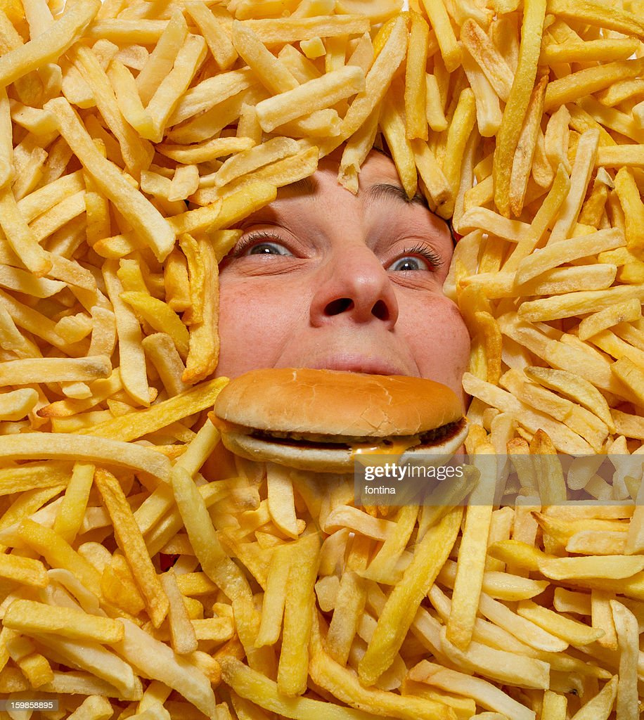 Drowning in junk food : Stock Photo